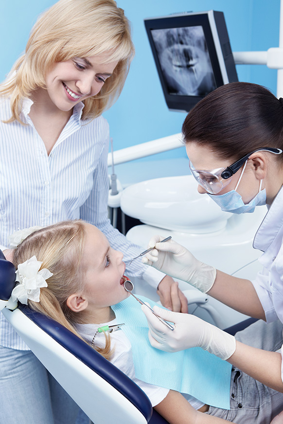 Child in dental chair receiving fluoride treatment