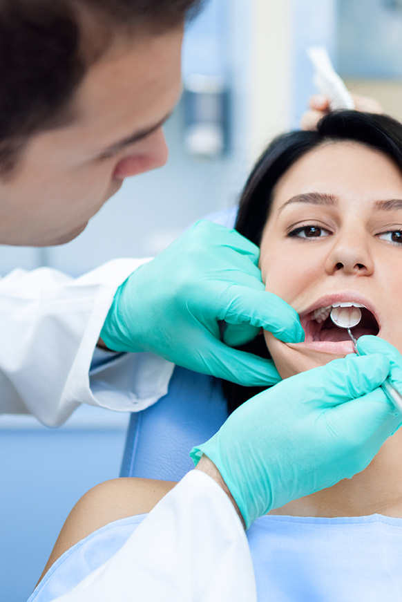 Young woman in dental chair with doctor