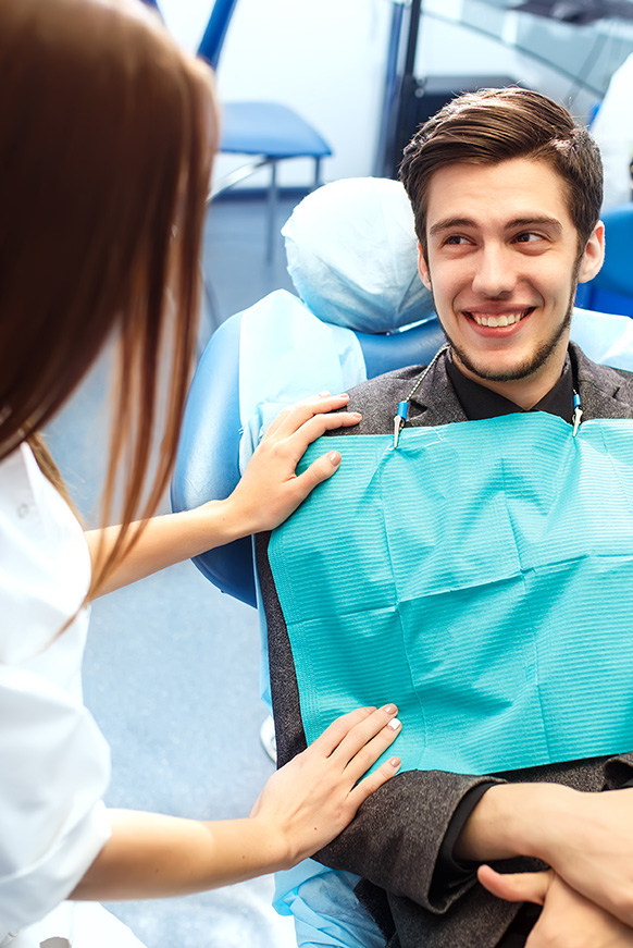 Man in dental chair smiling at doctor