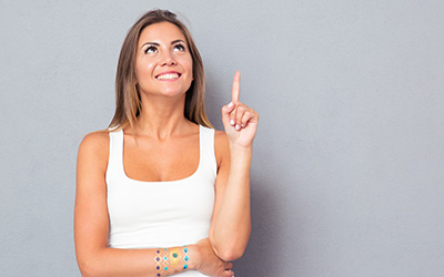 Woman with an smile looking up with an idea in mind