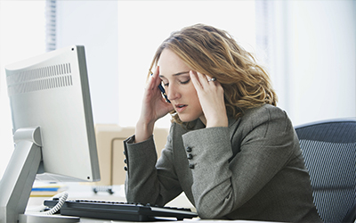 A woman at her computer looking stressed