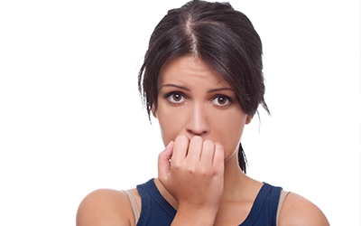 A woman biting her nails nervously